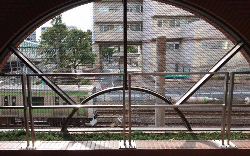 ブリックエンドの横にあるアーチ型の窓から見えるJR山手線