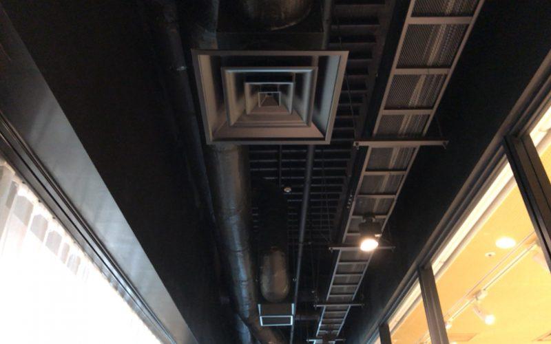 8/(ハチ)の排気ダクトや配管がむき出しになった天井
