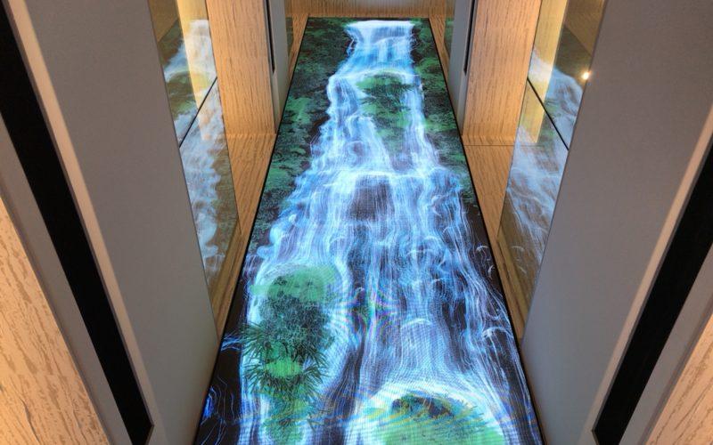 ギンザシックスの3F西階段から見上げたチームラボ Universe of Water Particles on the Living Wall
